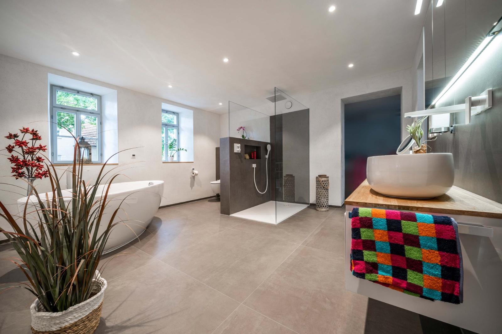 Badsanierung mit großflächigen Fliesen, Kalkputz, freistehender Badewanne, Urinal, spülrandloses WC und großer Duschfläche -3